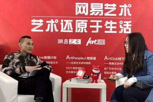 正在为记者介绍《匠心杯·2016中国琥珀雕刻设计大赛获奖作品集》.